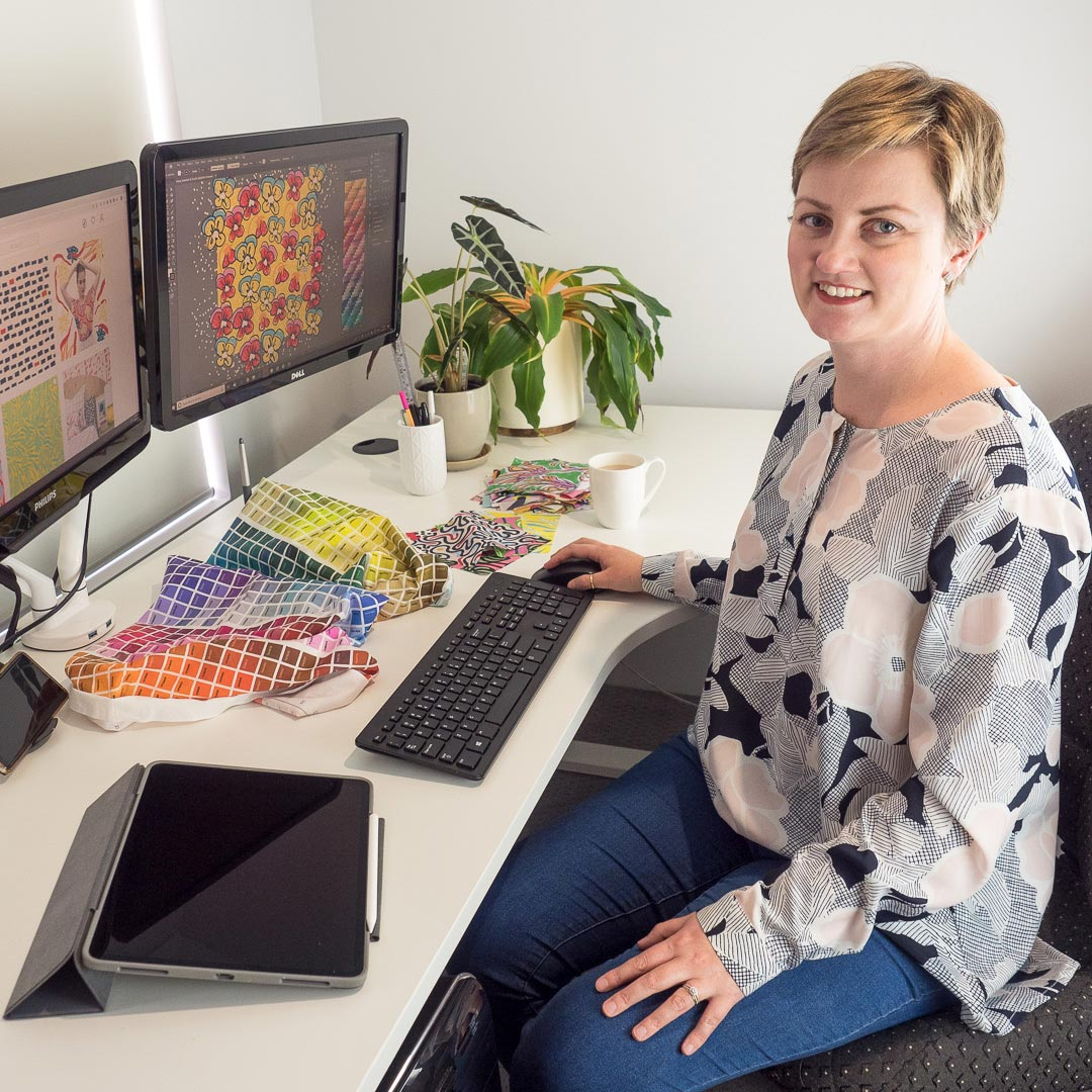 Profile photo of Louise sitting at the computer with colour swatches and ipad ready to design